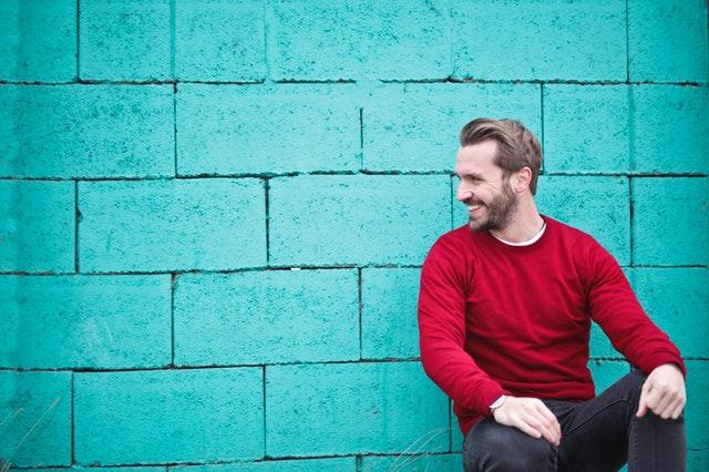 Muž v červenom svetri sediaci pred tyrkysovou stenou