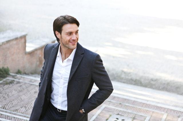 Muž v čiernom saku kráčajúci po schodoch