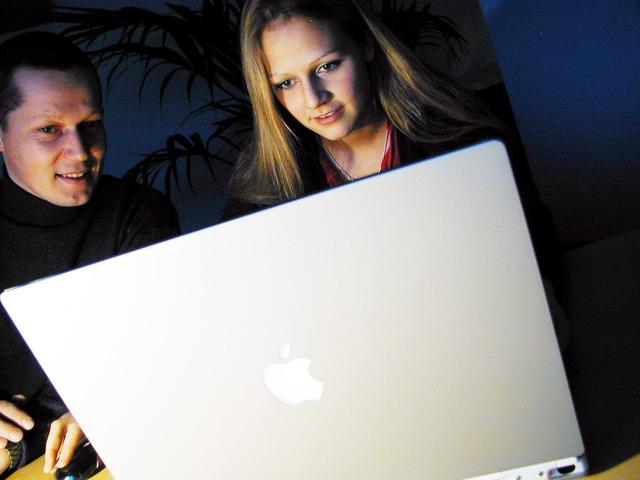 Pár, muž so ženou pozerajú do laptopu